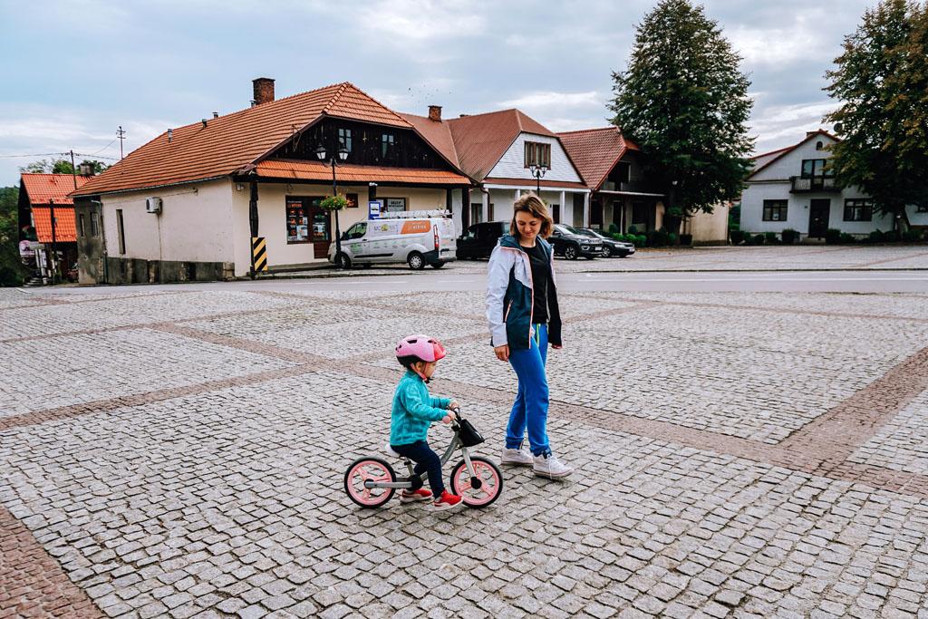 Dziecko jadące na rowerze po Rynku w Lipnicy Murowanej
