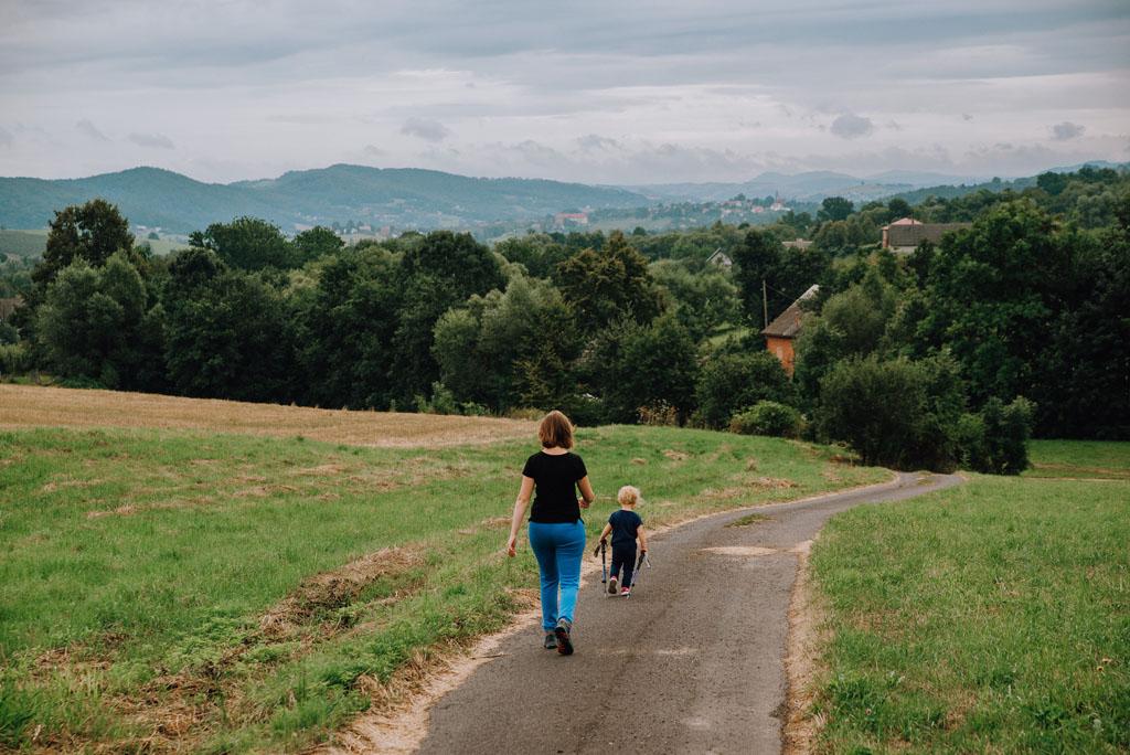 Mama z dzieckiem idą po drodze asfaltowej